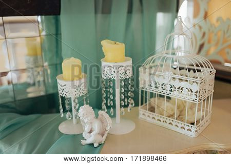 Stylish candlesticks with candles and a statue of an angel on the location of the wedding ceremony.