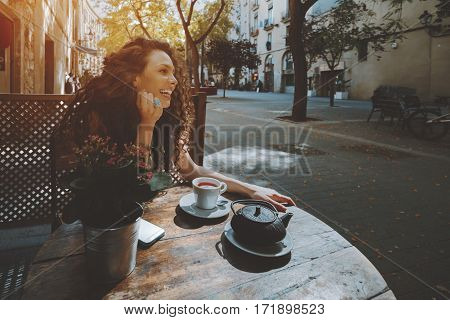 Laughing curly woman with black hair looking away while sitting in cafe during coffee break smiling hipster girl relaxing in street cafe female enjoying good day and drinking tea in street bar