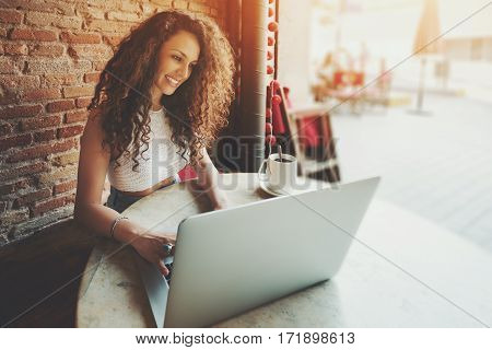 Smiling curly female student working on net-book with blank copy space screen for your text message or promotional content successful freelancer woman is using laptop computer while sitting in cafe