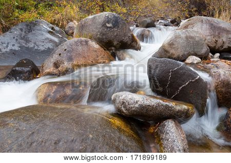The flow of water running among the rocks in the river bed