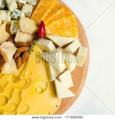 Cheese plate: Parmesan cheddar gouda mozzarella and other with chili pepper and almonds on wooden board on white background. Tasty appetizers. Top view. Square.
