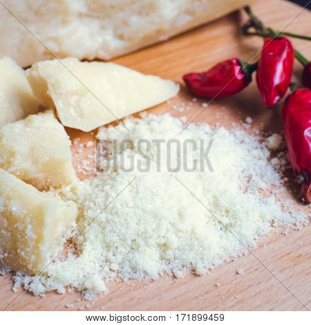 Grated Parmesan cheese with chili pepper on wooden chopping board on dark background. Tasty appetizers. Selective focus. Square.