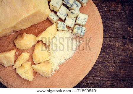 Grated Parmesan and sliced Blue cheese on wooden chopping board on old wooden background. Tasty appetizers. Top view.