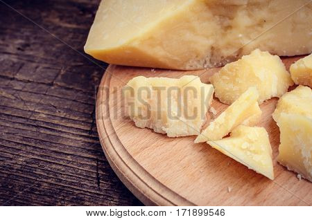 Parmesan cheese on wooden chopping board on old wooden background. Tasty appetizers. Selective focus.