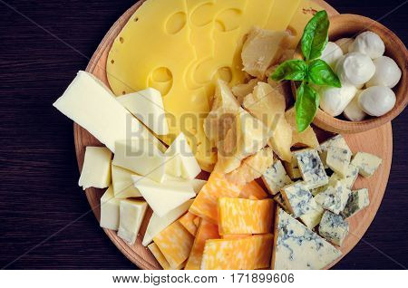 Cheese plate: Parmesan cheddar gouda mozzarella and other with basil on wooden board on dark background. Tasty appetizers. Top view.