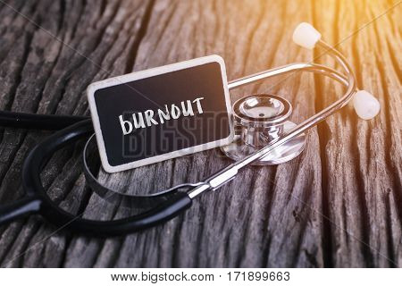 Stethoscope On Wood With Burnout Word As Medical Concept.