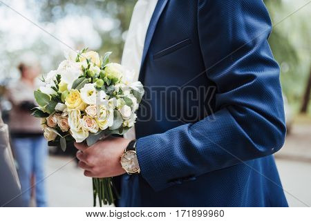 wedding bouquet in hands of the groom.