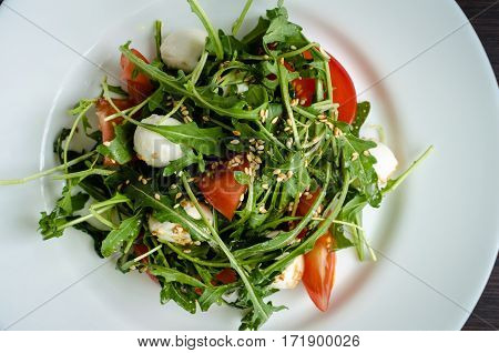 Fresh summer salad with tomatoes fresh arugula leaves mini mozzarella cheese and sesame seeds on white plate over dark wooden baclground. Healthy diet food concept. Top view.