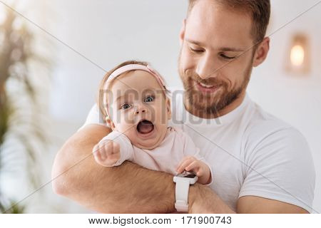 Exploring the world . Funny cute positive baby lying in hands of the young father and looking away while expressing interest and joy