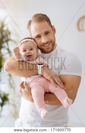 Exploring everything around. Funny cute joyful baby girl lying in hands of the father and looking away while expressing interest and joy