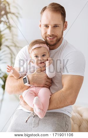 Fatherhood happiness . Joyful cute concentrated baby girl lying in hands of the young father and looking away while expressing positivity