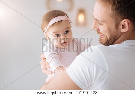 Cherishing every moment. Cheerful smiling bearded father standing at home and hugging the toddler girl while expressing tender emotions