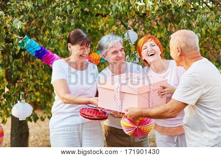 Seniors congratulate their friend with a birthday gift