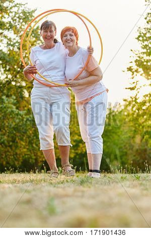 Two senior woman as friends with hoops in summer in the park