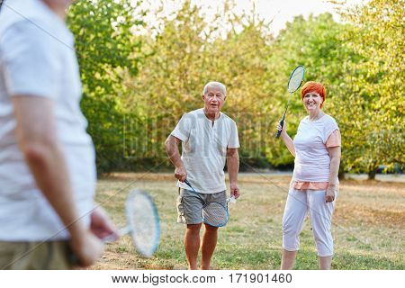 Group of seniors playing badminton in the park in summer