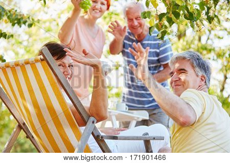 Group of senior friends having a party at the park in summer and waving