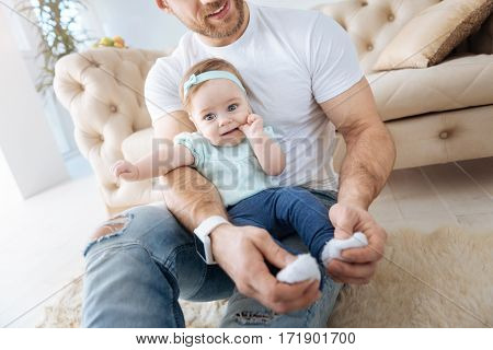 Pure cuteness. Happy delighted young father sitting at home and hugging his daughter while expressing positivity and touching her little feet