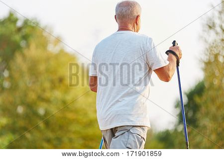 Senior man making a nordic walk for rehab in the nature