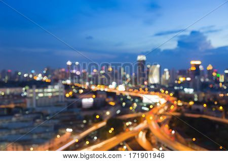 Blurred bokeh light aerial view city highway intersection with twilight sky abstract background