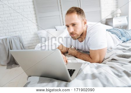 Enjoying my weekend. Delighted athletic charming man lying on the bed and using the laptop while expressing interest