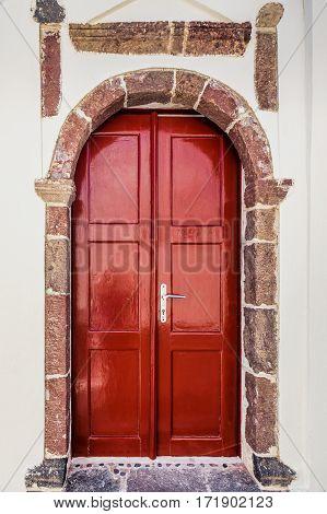 Picturesque red door with oval shaped door arche.