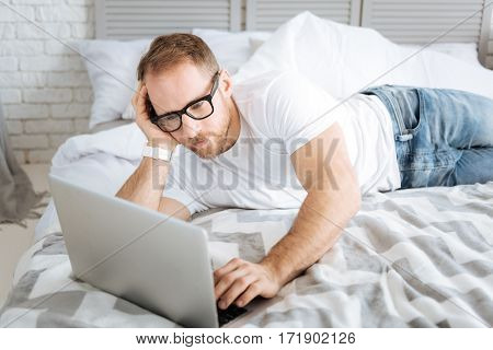 Doing my freelance job. Charismatic athletic charming man lying on the bed and using the laptop while expressing interest and surfing the Internet
