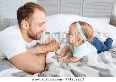 Finding happiness in everything. Funny cute positive baby lying on the bed with her father and looking on him while expressing interest and joy