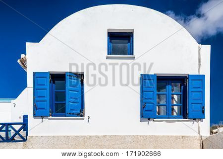Blue windows with blue shutters and blue fence on white house with oval roof.