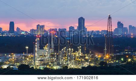 Oil refinery with city central business downtown background during sunset