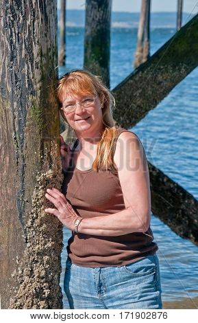 This portrait is a natural looking middle aged Caucasian woman in her fifties. She's wearing glasses blue jeans and a brown tank top and leaning against some ocean pillings with barnacles attached.