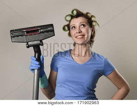 young funny maid domestic service woman or housewife with hair rollers and washing rubber gloves posing happy smiling cheerful holding vacuum cleaner enjoying the housework