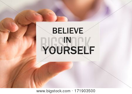 Businessman Holding Believe In Yourself Text Card
