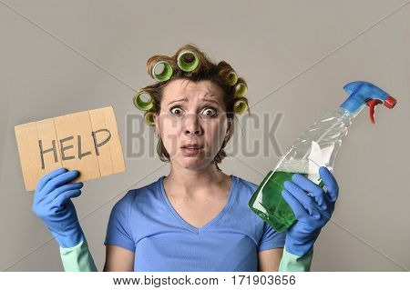 young overworked and frustrated service maid cleaning woman or lazy housewife in stress in hair rollers with washing spray bottle asking for help tired in housework concept