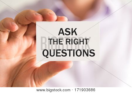 Businessman Holding Ask The Right Questions Card