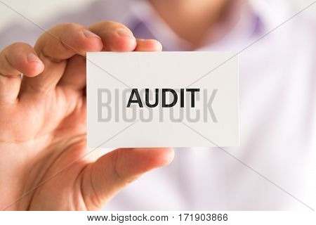 Businessman Holding A Card With Text Audit