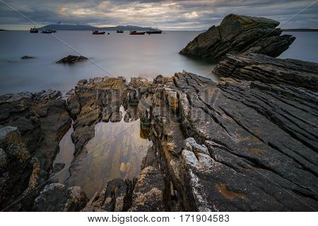 Rocks near Elgol with fishing boats on background in stormy weather Isle of Skye Scotland
