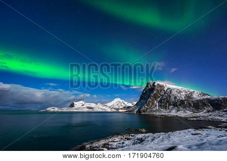 Aurora Borealis over Offersoykamen summit at Flaget coastline Lofoten
