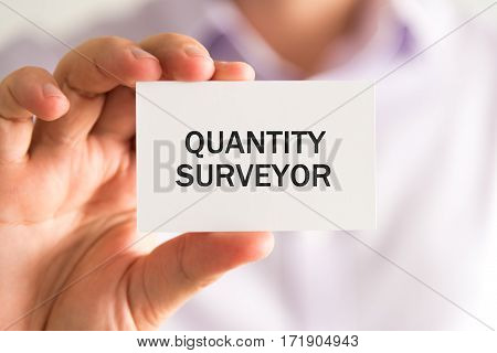 Businessman Holding A Card With Text Quantity Surveyor