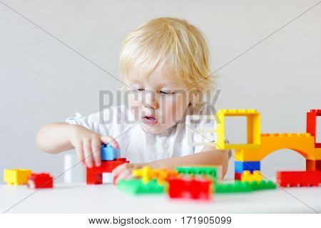 Toddler Boy Playing With Colorful Plastic Blocks
