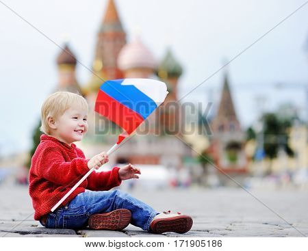 Toddler Boy Sitting And Playing With Russian Flag
