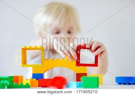 Toddler Boy Playing With Plastic Blocks, Focus On Hands