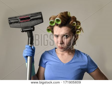 young angry and frustrated maid service woman or upset housewife with hair rollers cleaning gloves holding vacuum cleaner stressed in housework and housekeeping stress concept