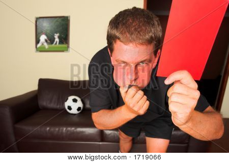 Referee In Sitting Room Blowing Whistle With Red Card