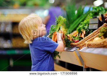 Cute Toddler Boy In Supermarket Choosing Fresh Organic Carrots