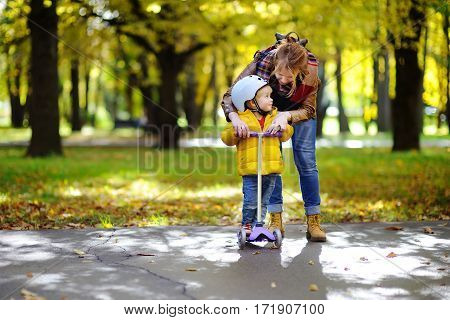 Young Mother Showing Her Toddler Son How To Ride A Scooter In A Autumn Park