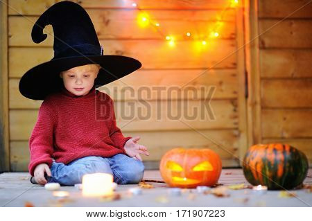 Little Wizard Playing With Halloween Pumpkins