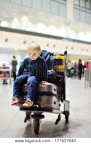 Tired little boy sitting on suitcases on international airport and waiting for flight and going on vacations