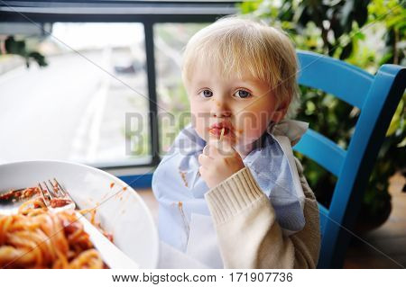 Cute toddler boy eating pasta in Italian indoors restaurant. Healthy/unhealthy food for little kids