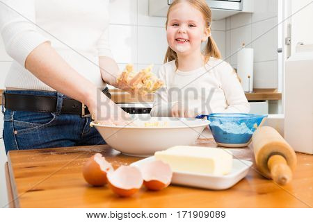 mother and daughter baking cookies at home