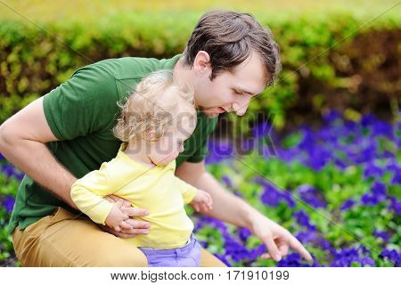 Cute toddler girl with her young father outdoors. Fatherhood concept